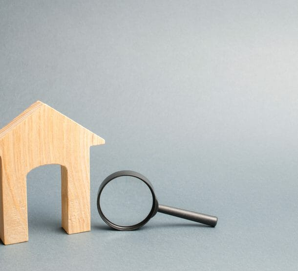 Wood cut out of house with magnifying glass