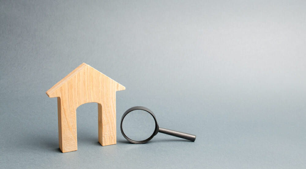 wood house and magnifying glass