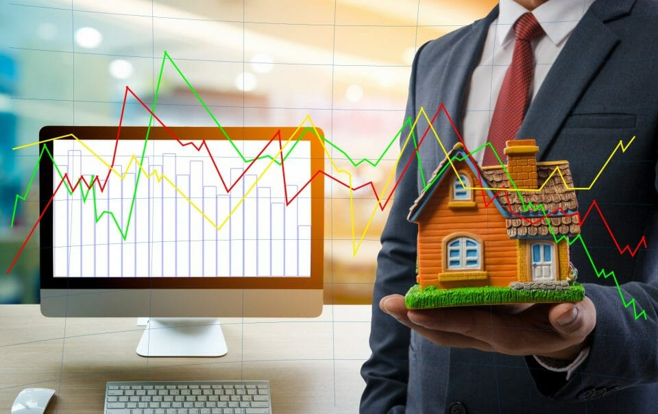 Stats and man holding model of house
