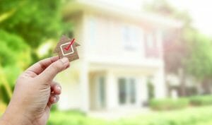 Person holding a tiny home with a checkmark in front of a house