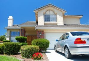 Large House with Shrubs and Car Parked in Driveway